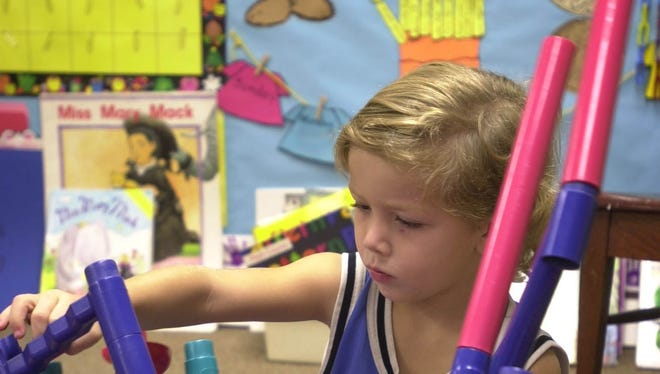 Pre-kindergarten student Douglas Shaffer, 5, concentrates on building a tower in his classroom at Adams Elementary School in Mesa, Ariz.