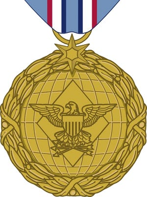 """This image released by the Department of Defense shows the obverse view with ribbon of the newly announced Distinguished Warfare Medal. The Pentagon is creating the new medal that can be awarded to troops who have a direct impact on combat operations but do it from afar. The medal will be awarded to individuals for """"extraordinary achievement"""" related to a military operation."""