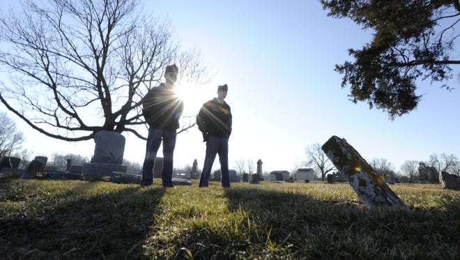 Missouri Military Academy cadets Tyler Vaughan and Kane Anderson look at a tilting marker on a veteran's grave at Elmwood Cemetery.