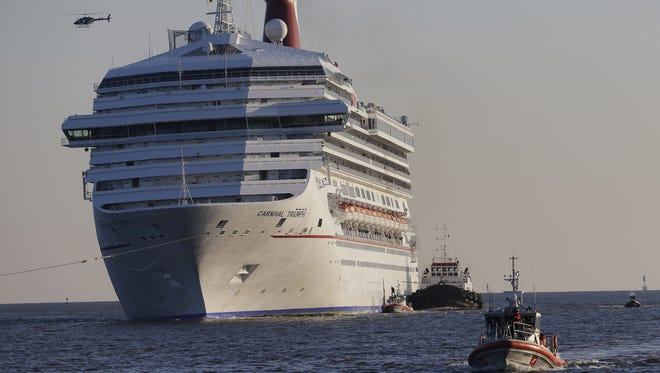 The Carnival Triumph is towed into Mobile Bay on Feb. 14 near Dauphin Island, Ala. The ship with more than 4,200 passengers and crewmembers was disabled Feb. 10 in the Gulf of Mexico after an engine room fire.