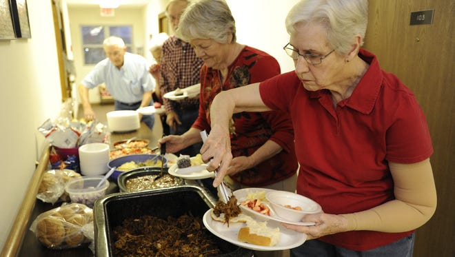 Mary Edwards serves herself barbecue beef at a Beef for Seniors dinner at the Holton Plaza senior apartments.