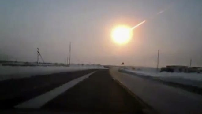 A meteor streaks across the sky in this frame grab made from a video done with a dashboard camera on a highway from Kostanai, Kazakhstan, to the Chelyabinsk region of Russia.