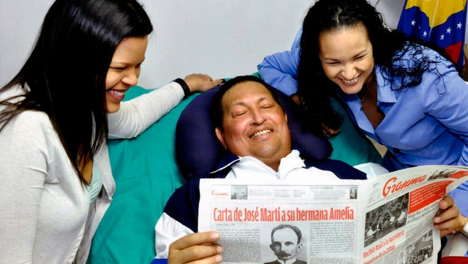 President Hugo Chavez, center, poses for a photo with his daughters Maria Gabriela and Rosa Virginia as he holds a copy of Cuba's state newspaper in Havana on Thursday.