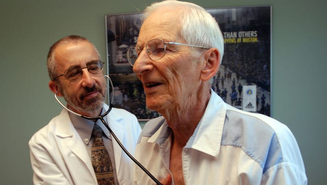 In this June 19, 2012 photo, Dr. Bruce Stowell examines patient Robert Busch at his office in Grants Pass, Ore.