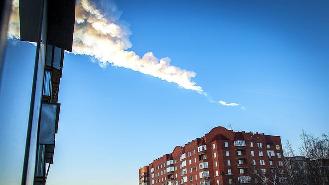 A meteorite left a smoke trail over an apartment building.