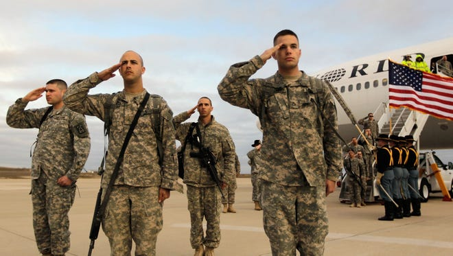 U.S. Army soldiers from the 2-82 Field Artillery, 3rd Brigade, 1st Cavalry Division, salute after walking off the plane as they arrive at their home base of Fort Hood, Texas after being part of one of the last American combat units to exit from Iraq.