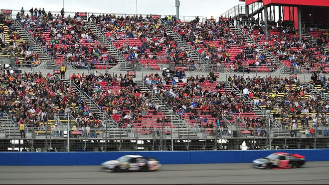 A less-than-full grandstand at Auto Club Speedway in Fontana, Calif., watches as Travis Kvapil (93) and Michael McDowell (98) drive by during the 2012 Auto Club 400.