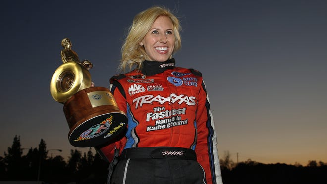 Courtney Force poses with the winner's trophy after racing to victory in Funny Cars Sunday at the NHRA Winternationals.