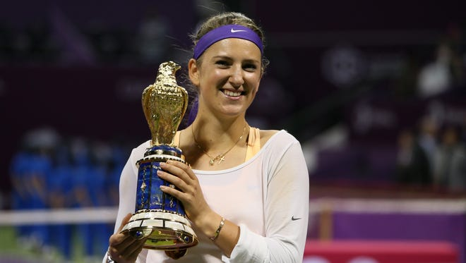 Victoria Azarenka shows off her trophy and flashes a smile after defeating Serena Williams in the final of the Qatar Open.