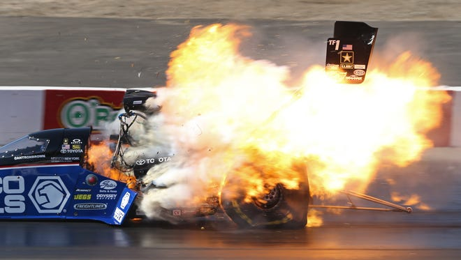 The Top Fuel dragster of Antron Brown explodes after crossing the finish line Sunday during eliminations for the NHRA Winternationals.