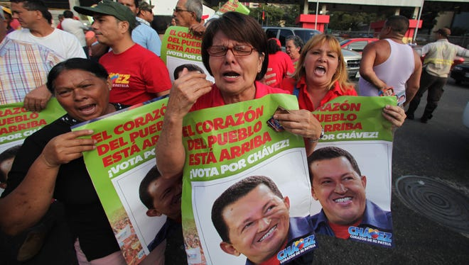 Supporters of Venezuela's President Hugo Chavez celebrate his return to the country outside the military hospital in Caracas, Venezuela, on Monday. Chavez arrived during the night after getting medical treatment in Cuba.