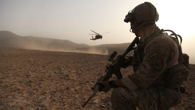 Staff Sergeant Thomas watches a Pave Hawk helicopter arrive in Kandahar, Afghanistan.