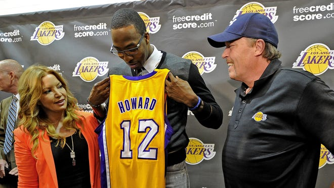 Siblings Jim and Jeanie Buss, who run the Lakers, talk with center Dwight Howard at the news confence introducing him. They now will own the Lakers officially as their father, Jerry Buss, has died.