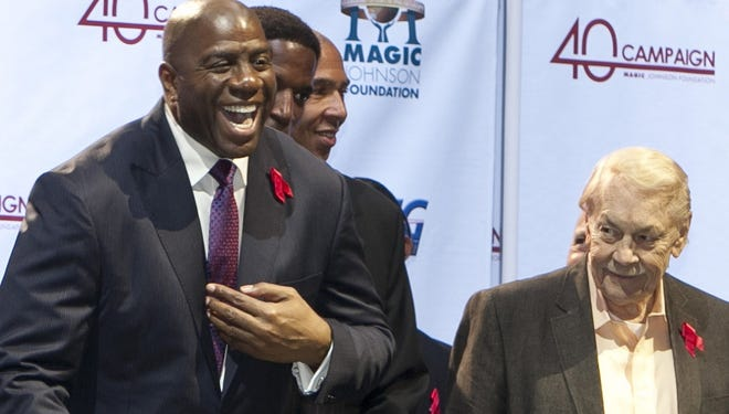 Los Angeles Lakers owner Jerry Buss, without the tie, looks towards Magic Johnson during a ceremony of the Magic Johnson Foundation in Los Angeles in November 2011.