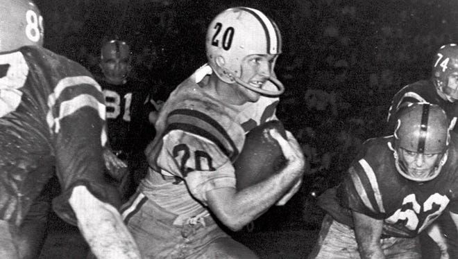 LSU's Billy Cannon (20) slips by tacklers at the start of an 89-yard punt return for a touchdown against Mississippi on Nov. 1, 1959, in Baton Rouge.