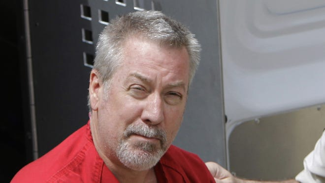 Former Ill., police sergeant Drew Peterson arrives at the Will County Courthouse for his arraignment on charges of first-degree murder in the 2004 death of his former wife Kathleen Savio, who was found in an empty bathtub at home.