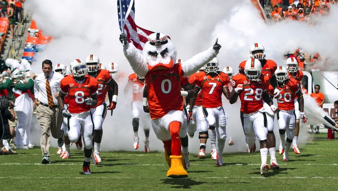 University of Miami's mascot Sebastian the Ibis leads players onto the field before a NCAA college football game against North Carolina State in Miami. The Hurricanes football program has been at the center of an investigation for two years, an investigation that has led to one of the biggest controversies in NCAA history.