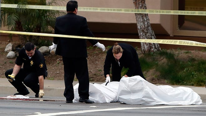 Orange County coroner's officials remove a body from a street in Orange, Calif., on Tuesday.