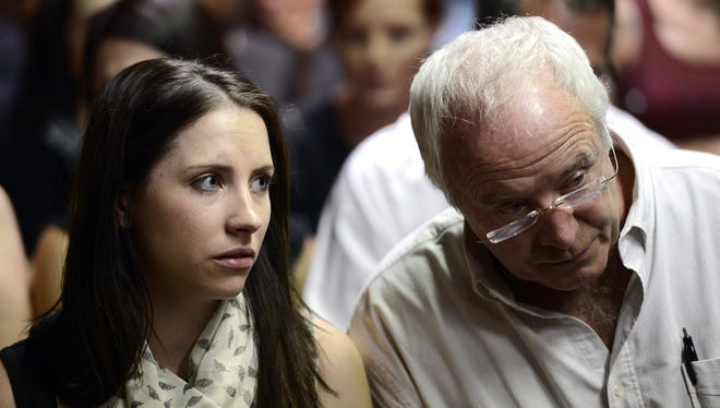 The father of South African Olympic sprinter Oscar Pistorius, Henke, and his sister, Aimee, watch the court proceedings on Tuesday in Pretoria.