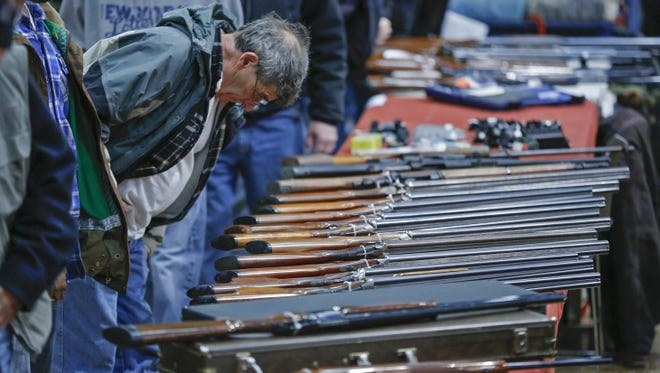 A customer looks over shotguns on display at the annual New York State Arms Collectors Association Albany Gun Show on Jan. 26, 2013.