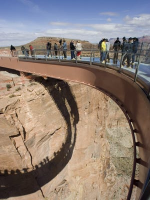 Tourists walk on the glass-bottomed Skywalk that extends 70 feet over the edge of Grand Canyon West's Eagle Point in northwestern Arizona.