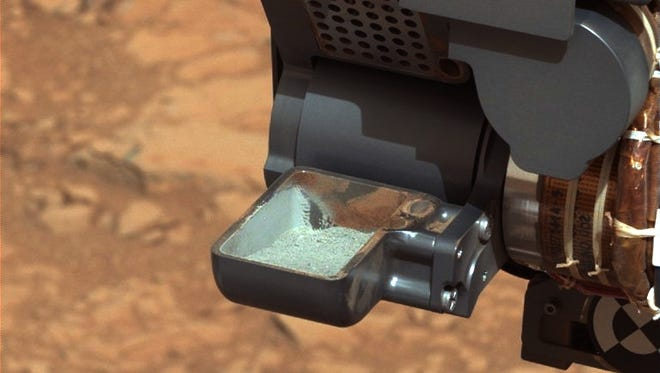 This image from NASA's Curiosity rover shows the first sample of powdered rock extracted by the rover's drill. The image has been white-balanced to show what the sample would look like if it were on Earth.