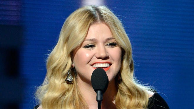 Kelly Clarkson, shown at the Grammys, defends herself online against criticisms in Clive Davis' book.