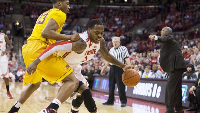Ohio State Buckeyes forward Deshaun Thomas fights his way past Minnesota Golden Gophers forward Rodney Williams as Minnesota Golden Gophers head coach Tubby Smith tries to direct his defense at the Schottenstein Center.