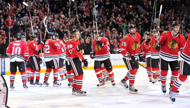 The Chicago Blackhawks celebrate a victory against the Vancouver Canucks at the United Center. The Blackhawks tied an NHL record for scoring at least one point in 16 consecutive games to open a season.