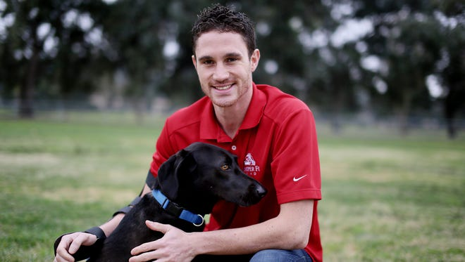 Brandon Pelletier sits with his dog Skylar at a park near his home in Chula Vista, Calif.,  on Tuesday.