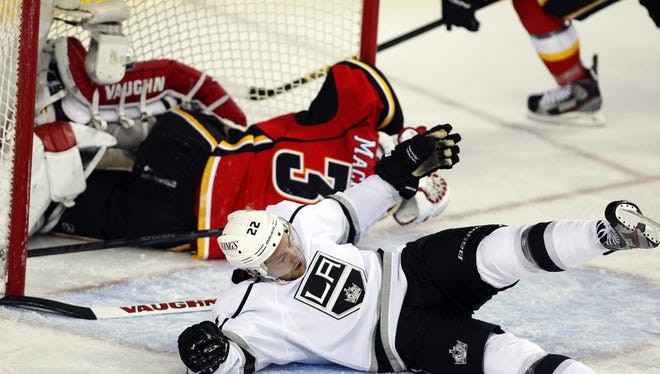 Los Angeles center Trevor Lewis crashes to the ice after colliding with Flames goalie Joey MacDonald during the second period. The Kings beat the Flames 3-1.