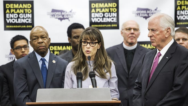 Actress Amanda Peet delivers remarks as U.S. Rep Elijah Cummings, left, and entertainer Chris Rock, rear, look on during a press conference by Mayors Against Illegal Guns Feb. 6 on Capitol Hill.