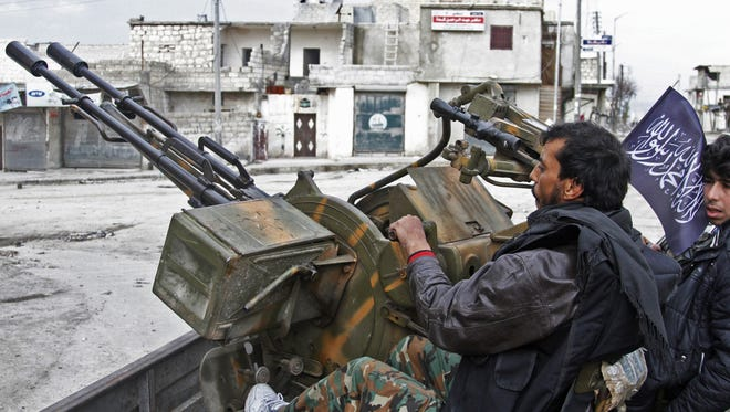 Free Syrian Army fighters sit behind their anti-aircraft weapon in Aleppo, Syria, on Feb. 9.