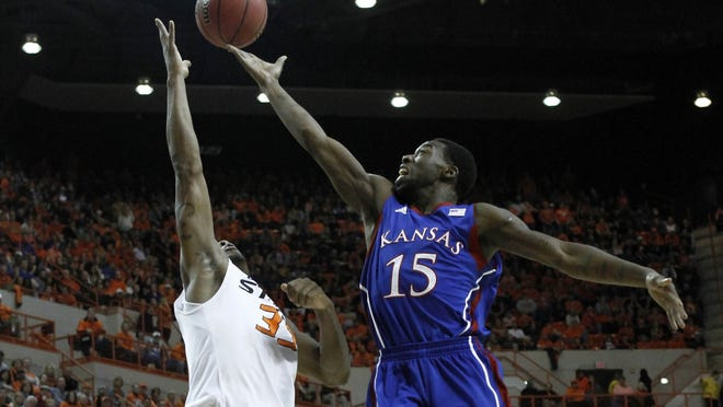 Kansas guard Elijah Johnson (15) goes up for a basket over Oklahoma State guard Marcus Smart (33) during the second half at Gallagher-Iba Arena. Kansas won 68-67 in double overtime.