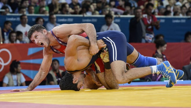 Coleman Scott (USA), in red, wrestles with Toghrul Asgarov (AZE) in the men's 60kg freestyle wrestling semifinals during the London 2012 Olympic Games.