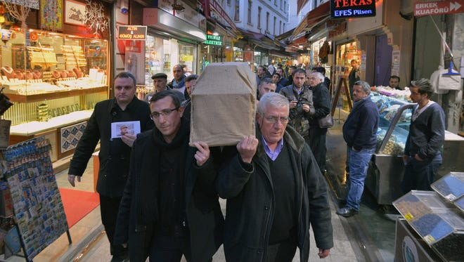 A casket bearing the body of Sarai Sierra is carried to an ambulance in Istanbul Feb. 6. The man at left is holding a photo of the slain  33-year-old New York woman.