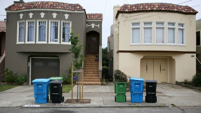 Trash, recycling and compostable material bins sit in front of homes in San Francisco in this file photo.