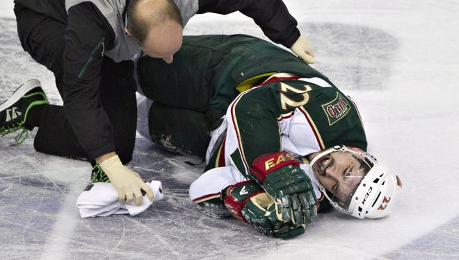 Minnesota Wild's Cal Clutterbuck is tended to by a trainer after being hit by Edmonton Oilers Taylor Hall during third period on Thursday night.