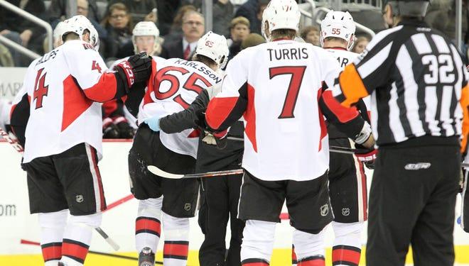 Ottawa Senators defenseman Erik Karlsson (65) is helped off the ice after being injured on Feb. 13.