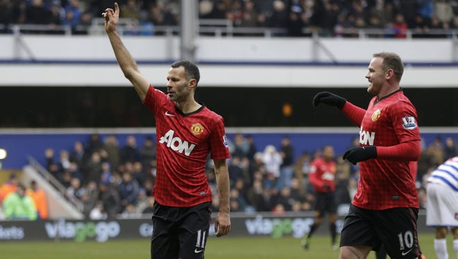 Manchester United's Ryan Giggs (left) celebrates with his teammate Wayne Rooney (right) after he scored against Queens Park Rangers, during their English Premier League soccer match at Loftus Road ground in London.  Manchester United would go on to win the match, 2-0.
