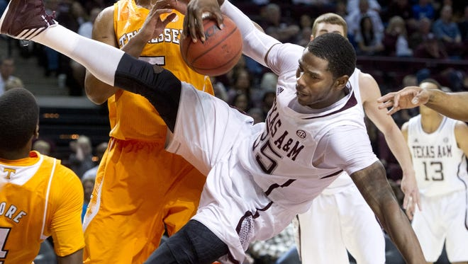 Texas A&M's Ray Turner comes down with the ball in front of Tennessee's Jarnell Stokes after being fouled by Tennessee's Armani Moore, left, during the first half.