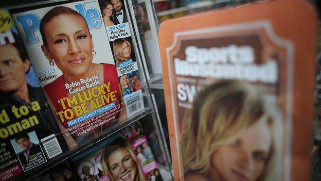 Issues of People magazine are displayed next to a Sports Illustrated ad on a New York City newsstand earlier this month. Time is in talks to sell most of its magazine group, including People and Entertainment Weekly, to the Meredith Corp. However, it is expected to retain control of flagship titles Time, Sports Illustrated and Fortune.
