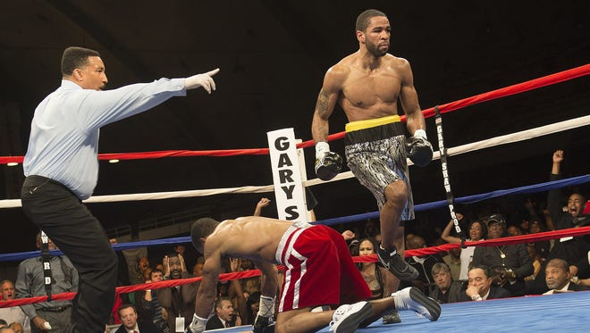 Lamont Peterson heads to a neutral corner after knocking down Kendall Holt in the fifth round  of their IBF Junior Welterweight World Championship Saturday in Washington, D.C.