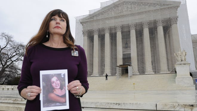Jayann Sepich stands in front of the Supreme Court holding a photograph of her daughter Katie.