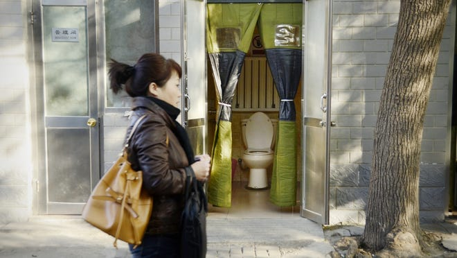 A woman walks past a neighborhood toilet. Public restrooms now must meet stricter standards.