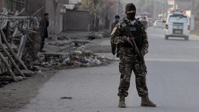 Security official stands guard the scene of a suicide car bomb attack which killed and injured several people at the National Directorate of Security in Jalalabad, Afghanistan, on  Sunday.