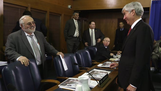 Michigan Gov. Rick Snyder, right, greets the chairman of the Michigan Senate Appropriations Committee, Republican Roger Kahn of Saganaw, Mich., before presenting his budget Feb. 7 to the Legislature in Lansing, Mich.