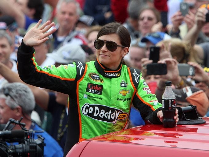 Danica Patrick waves to the crowd as she is introduced before the 2013 Daytona 500 at Daytona International Speedway.