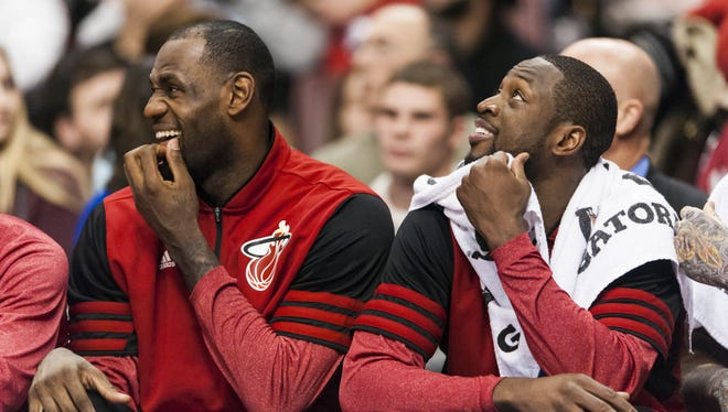 Heat stars LeBron James and Dwyane Wade watch from the bench during Sunday's win against the Cavaliers, their 11th in a row.