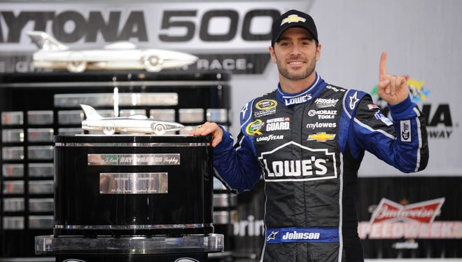 Jimmie Johnson poses with the Harley J. Earl Trophy after winning the 2013 Daytona 500 on Sunday.